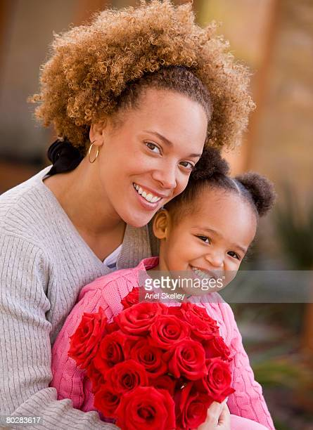 African mother and daughter hugging with flowers