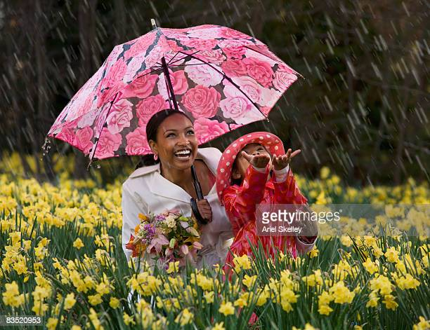 African mother and daughter playing in the rain