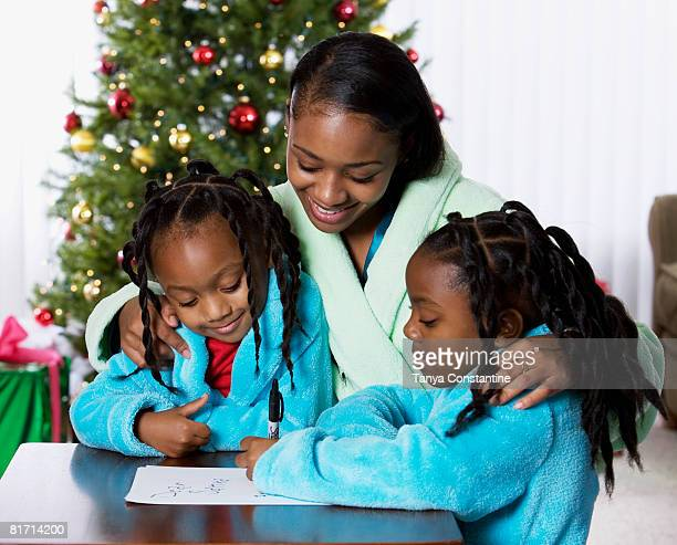 African mother and daughters writing letter to Santa Claus