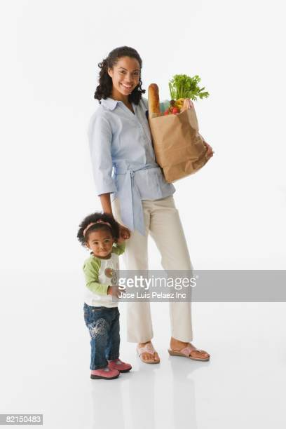 African mother holding baby?s hand and grocery bag