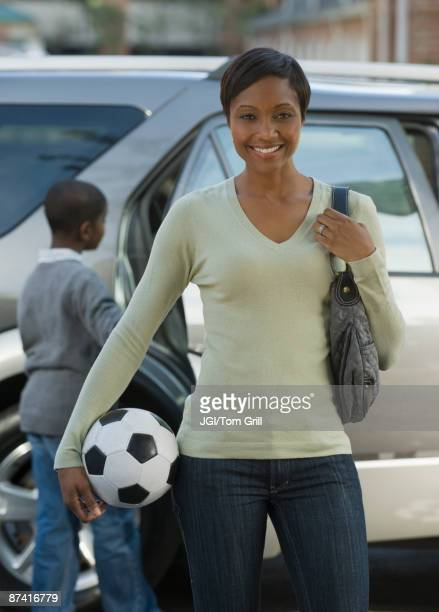 African mother holding soccer ball