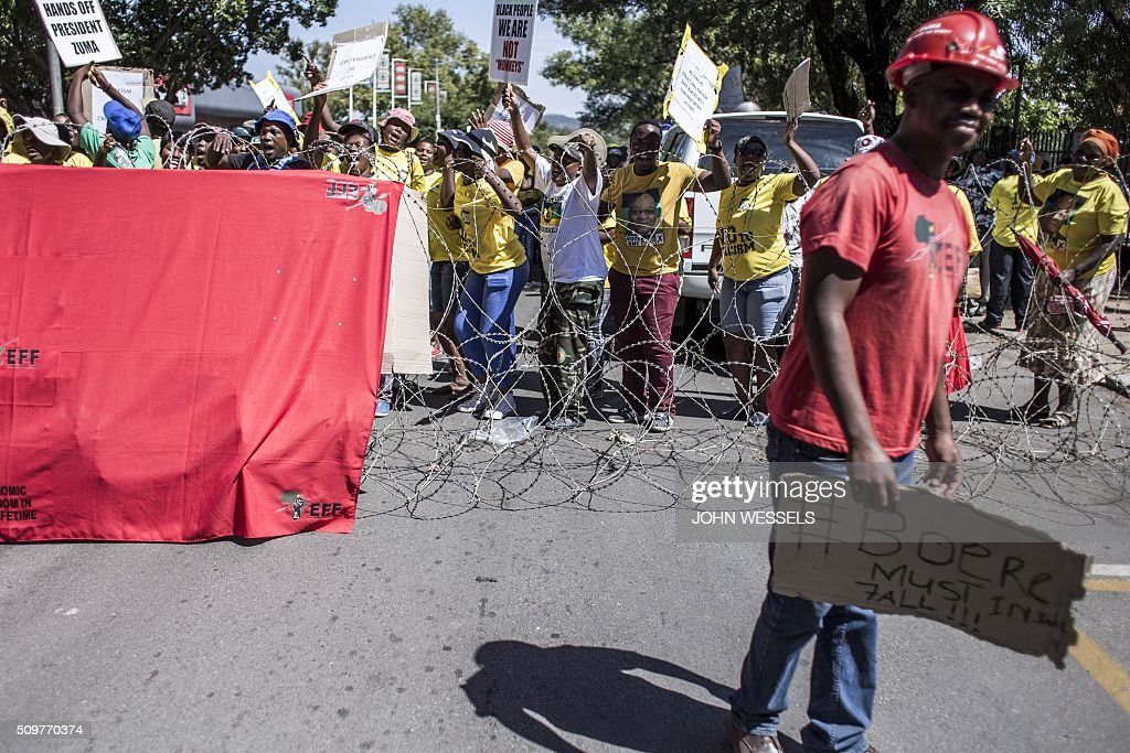 African National Congress(ANC) and Economic Freedom Fighters(EFF) supporters dance and sing outside of the Magistrates Court in Parys, Freestate, on February 12, 2016, in protest against racism and the murder of two farm workers. / AFP / JOHN WESSELS