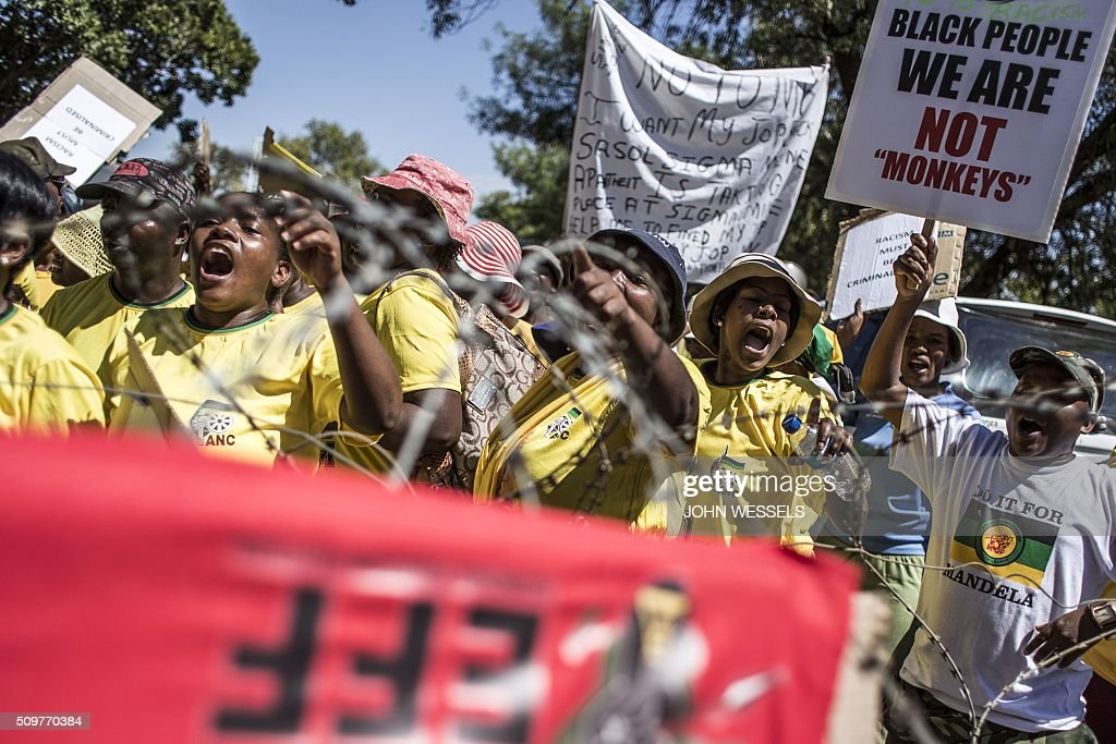 African National Congress(ANC) and Economic Freedom Fighters(EFF) supporters dance and sing outside of the Magistrates Court in Parys, Freestate, on February 12, 2016 in protest against racism and the murder of two farm workers. / AFP / JOHN WESSELS