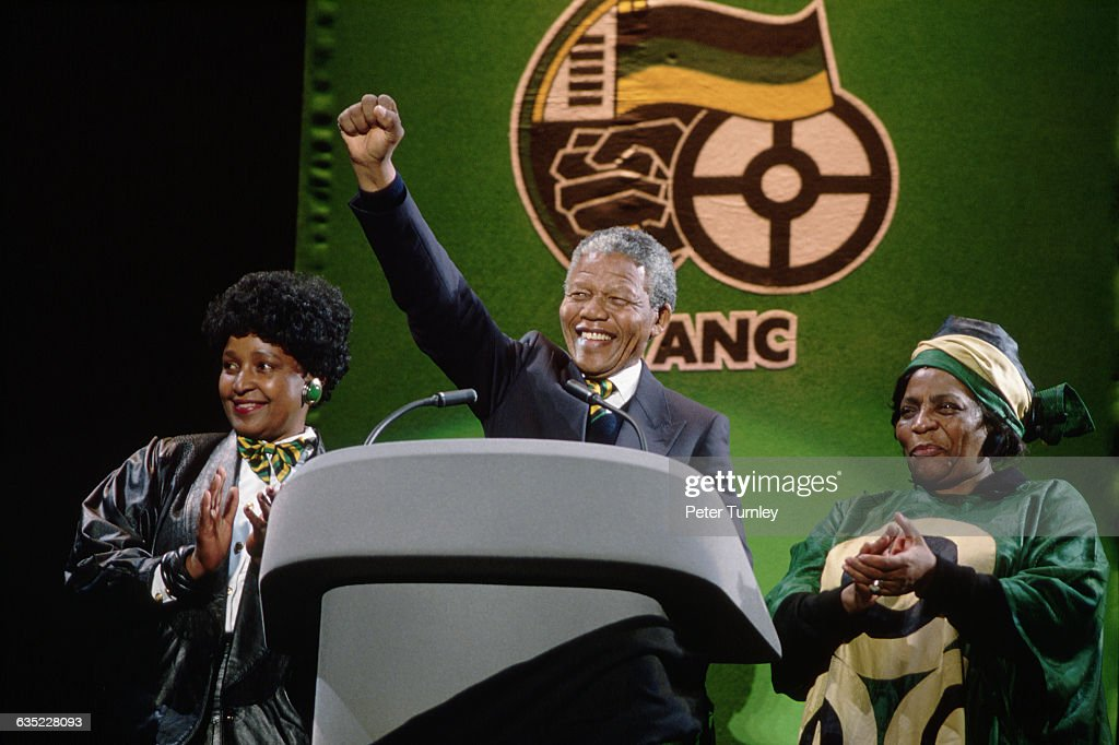 African National Congress leader Nelson Mandela raises his fist at London rally shortly after his release from prison His wife Winnie Mandela and ANC...