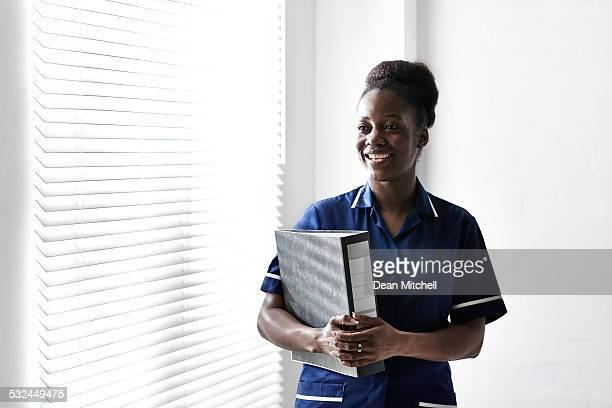 Africana sonriente enfermera con archivo