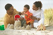 African parents and toddler building sand castle at beach