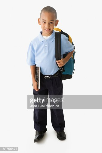 African school boy in uniform holding backpack and notebook