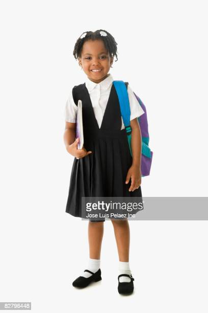 African school girl in uniform holding backpack and notebook