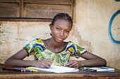Portrait of an African ethnicity schoolgirl (age 13) in an educational environment in Bamako, Mali learning her lesson outdoors sitting on a desk and slightly smiling.