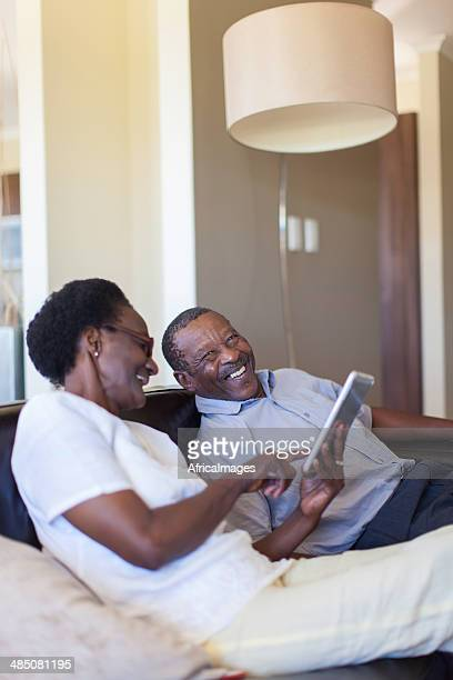 African senior couple laughing, working on a digital tablet together