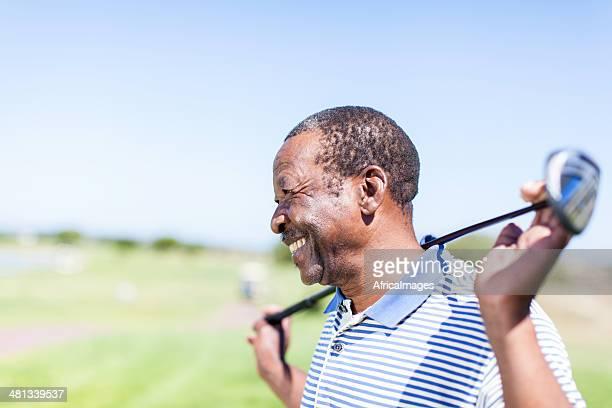Afrique senior golfeur tenant son club avec un grand sourire.