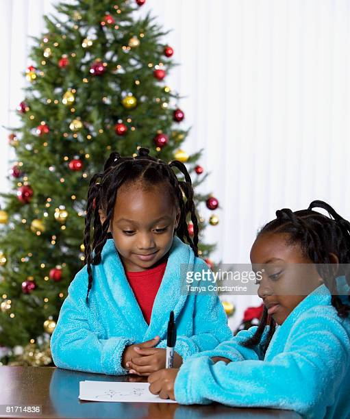 African sisters writing letter to Santa Claus