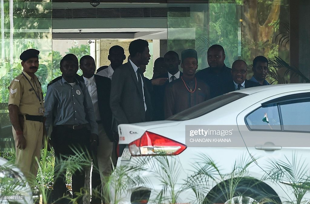 African student union representatives and members of African delegations are watched by an Indian security official (L) as they leave the Ministry Of External Affairs in New Delhi on May 31, 2016, after a meeting with India's Minister of External Affairs Sushma Swaraj following a series of assaults on African residents in India. Police said May 29, that they have arrested five Indians accused of assaulting Africans in New Delhi, after African diplomats urged the Indian government to ensure the safety of their nationals living in the country. / AFP / CHANDAN