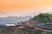 Rural village with one person walking in distance next to a red and blue fence between houses at sunset Lalibela Ethiopia Horn of Africa