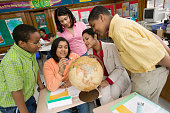 African teacher and students looking at globe