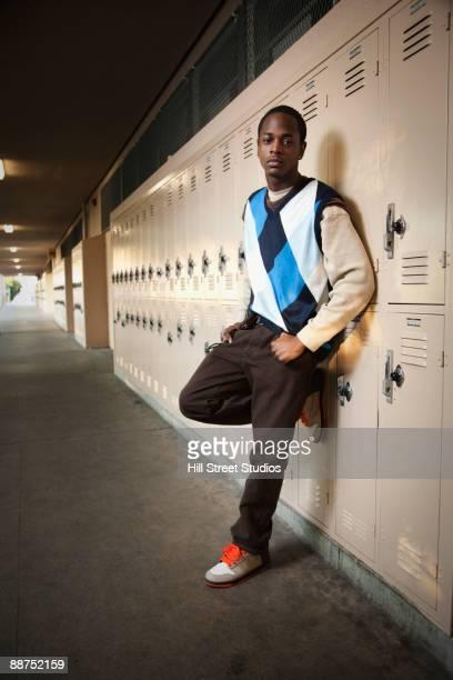 African teenage boy leaning on lockers in school hallway