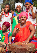 Traditional africans singing, while the two mature ladies play the drums, happy smiling and content; focus on the girls. [url=file_closeup.php?id=17684736][img]file_thumbview_approve.php?size=1&id=176