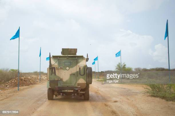 African Union troop carriers travel on a road that is flagged by national flags on May 01 2017 in Baidoa Somalia