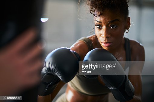african woman boxing with punching bag in garage gym : Stock Photo