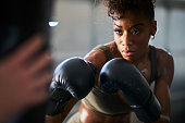 african woman boxing with punching bag in garage gym close up