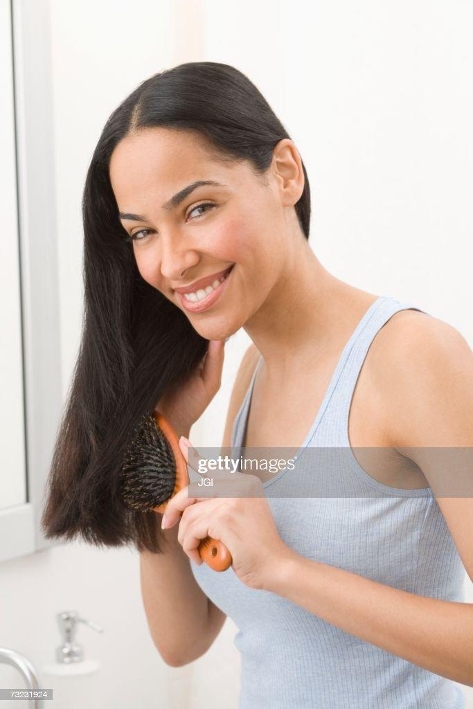 African woman brushing hair in bathroom