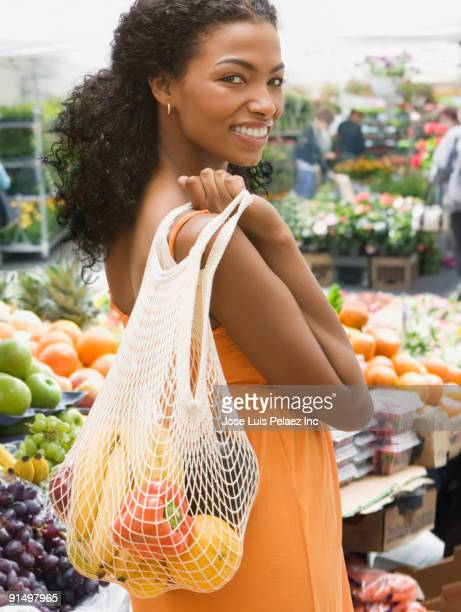 African woman carrying bag of fruits and vegetables
