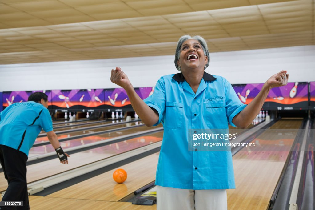 African woman cheering in bowling alley