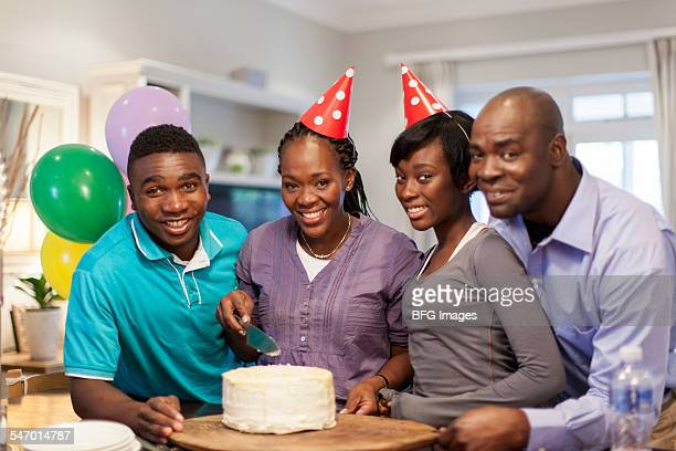 African woman cuts into her birthday cake surrounded by her family, Cape Town, South Africa