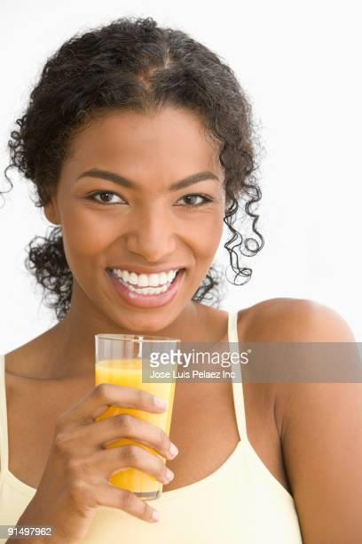 African woman drinking orange juice