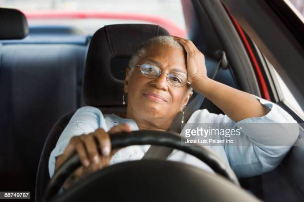 African woman driving car in traffic