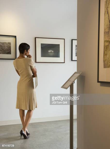 African woman enjoying photographs in museum