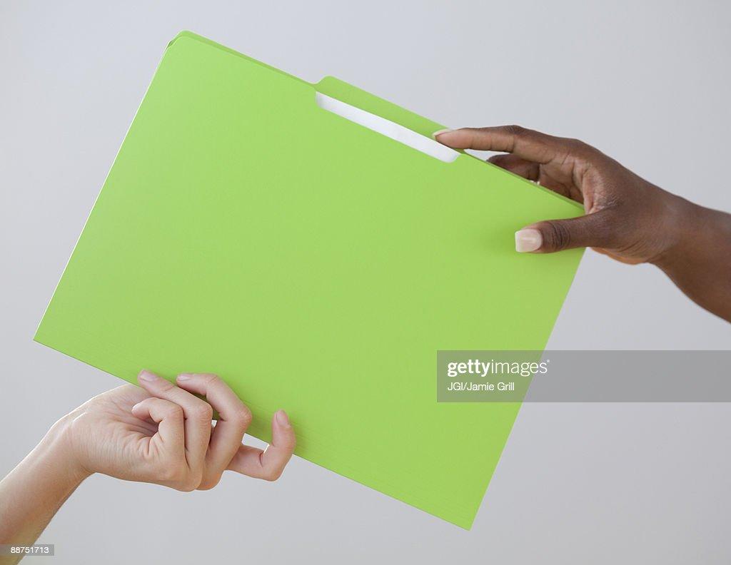 African woman handing co-worker a folder : Stock Photo