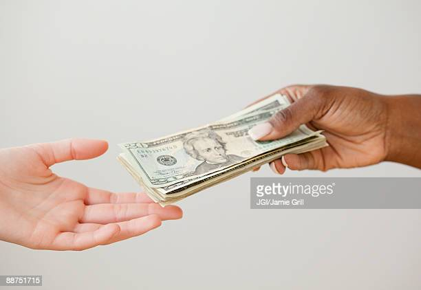 African woman handing over stack of 20 dollar bills