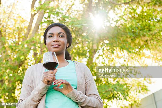 African woman having a glass of wine.