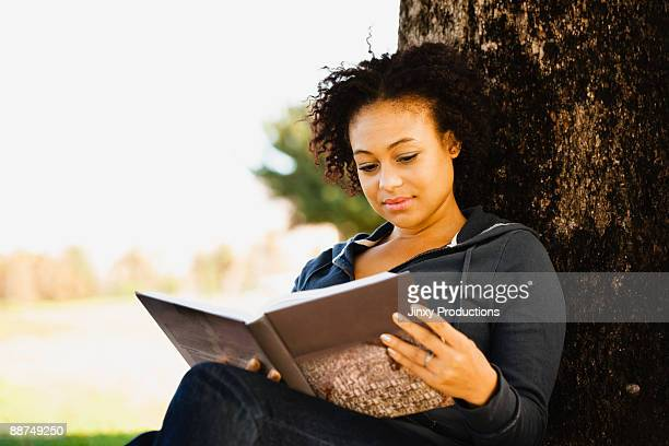 African woman holding book under tree