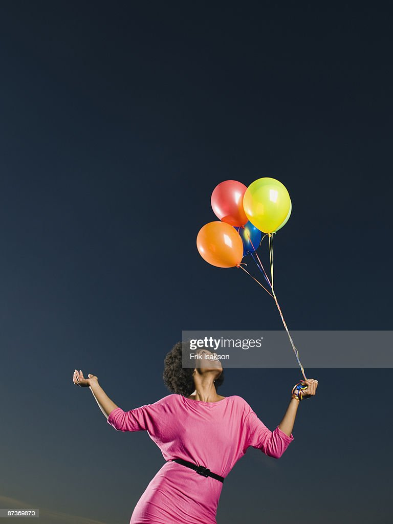 African woman holding bunch of balloons stock photo getty images