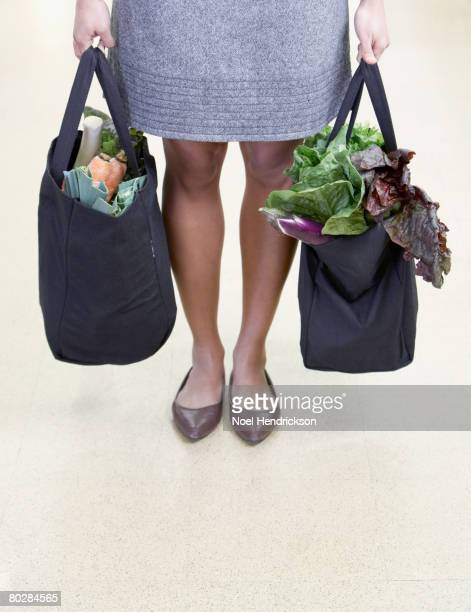 African woman holding reusable grocery bags