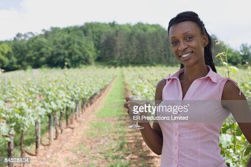 African woman holding wine glass in vineyard : Stock Photo