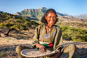 African woman is sifting the sorghum, East Africa