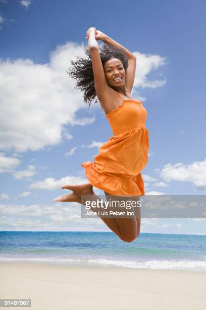 African woman jumping in mid-air at beach