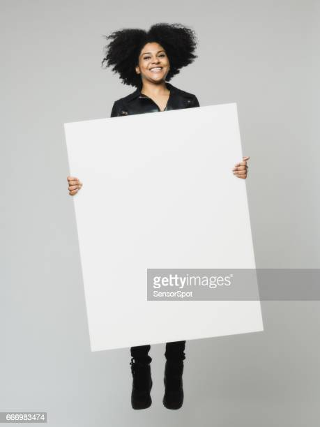 African woman jumping with a blank billboard