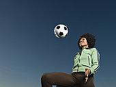 African woman kneeing soccer ball