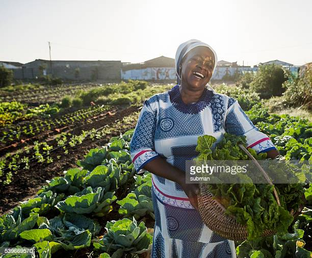 African woman laughing in vegetable garden