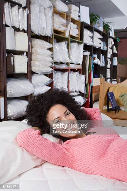 African woman laying on bed in store