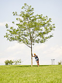 African woman leaning against tree in park