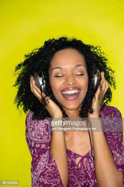 African woman listening to headphones