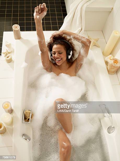 African woman listening to music in bath