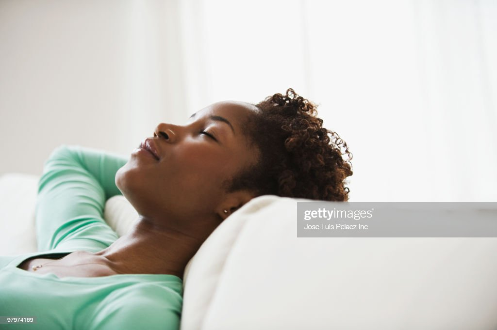 African woman napping on sofa
