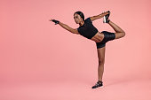 African woman practicing yoga in studio. Female athlete standing in Natarajasana yoga exercise pose over pink background. Lord of the dance pose yoga in studio with copy space.