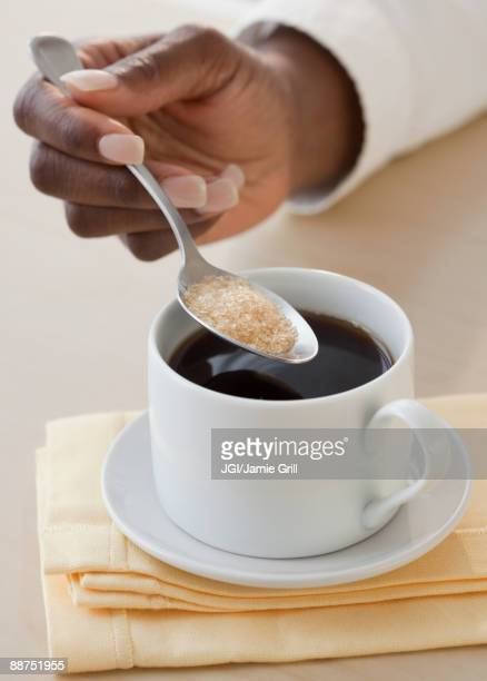 African woman putting sugar in coffee